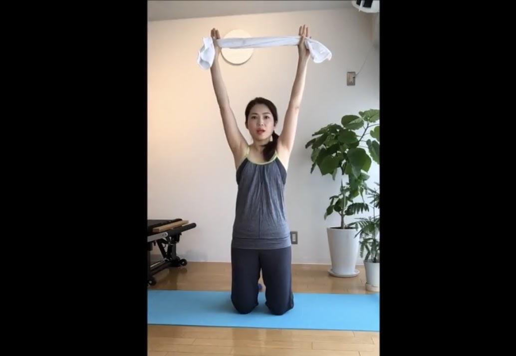 タオルを肩幅よりも広い位置でつかみ頭上に持ち上げる
